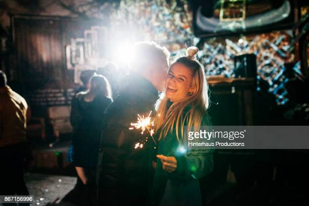 Girl Laughing With Boyfriend While Holding Sparkler At Open Air Nightclub