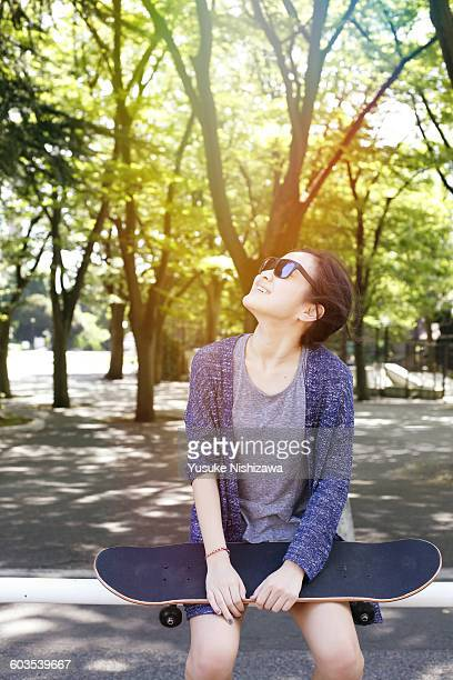 girl laughing with skateboard - yusuke nishizawa stock pictures, royalty-free photos & images