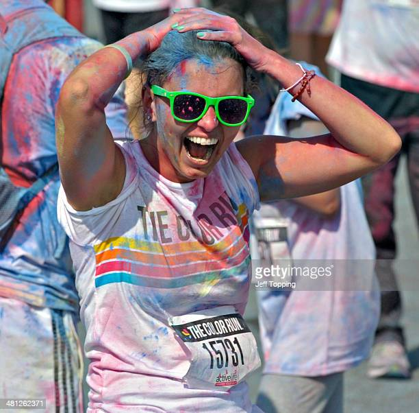 A girl laughs after having blue chalk thrown on her at one of four chalk stations at The Color Run presented by Active life dubbed the Happiest 5km...