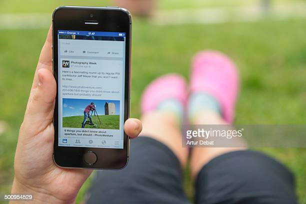 Girl lay on backyard house grass checking internet with smartphone