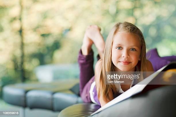 girl laying down and reading book - 8 9 jaar stockfoto's en -beelden