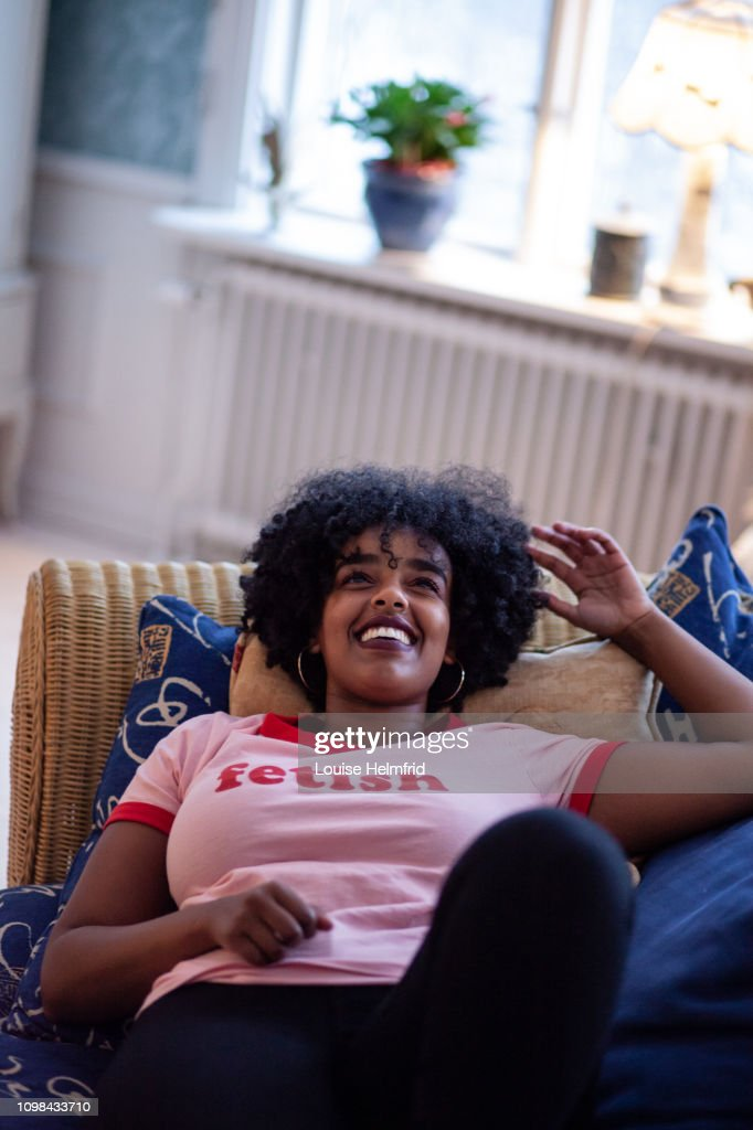 Girl laying in couch smiling : Stock Photo