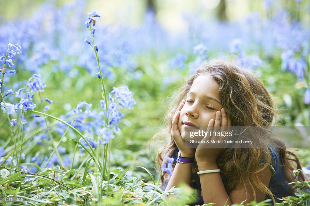 Girl laying in field of flowers : Stock Photo