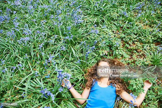 Girl laying in field of flowers