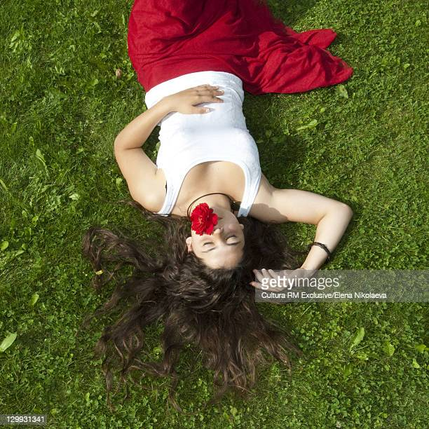 Girl laying in grass with flower