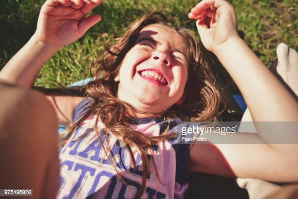 a girl laying in the grass laughing. - innocence stock pictures, royalty-free photos & images