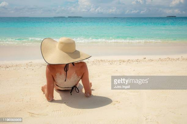 girl laying on a beach in the maldives - girls sunbathing stock pictures, royalty-free photos & images