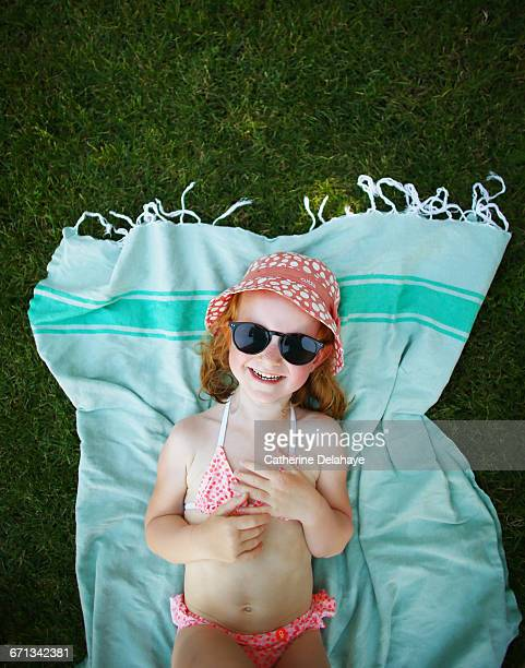 A girl laying on a towel on the grass