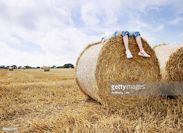 Girl laying on bale of hay