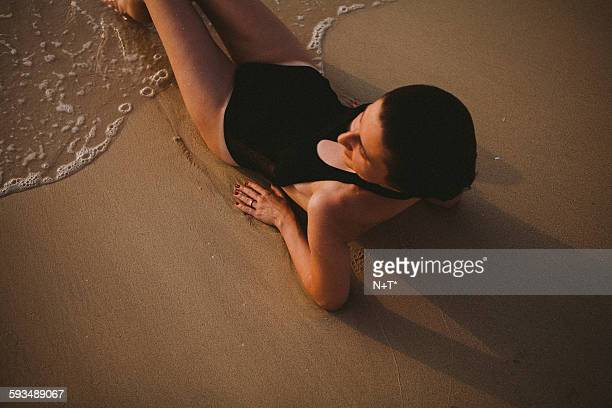 girl laying on beach - n n girl model stock photos and pictures