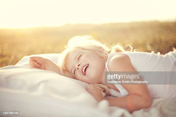 Girl laying on bed in sunlight
