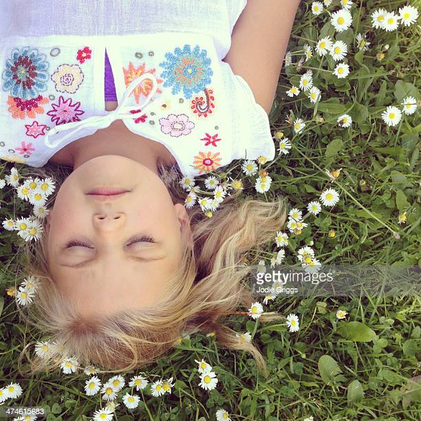 Girl laying on grass surrounded by daisies