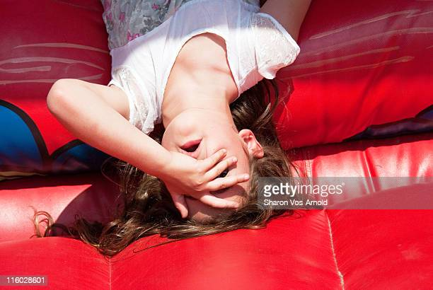 Girl laying on red bouncy castle