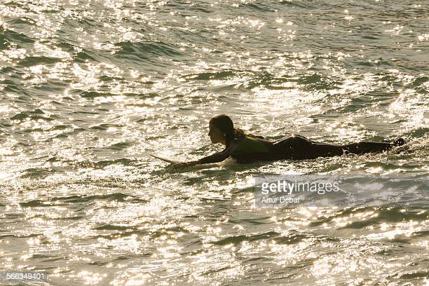 Girl laying on surf board rowing with hands and the sun reflected on the Mediterranean Sea in the Barcelona shoreline. Vilassar de Mar, Catalonia,...