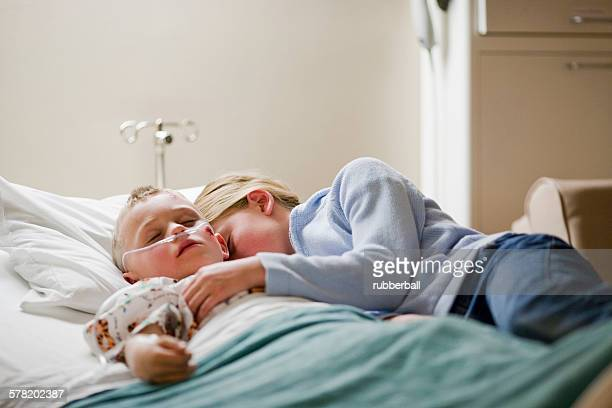 Girl laying with brother on hospital bed