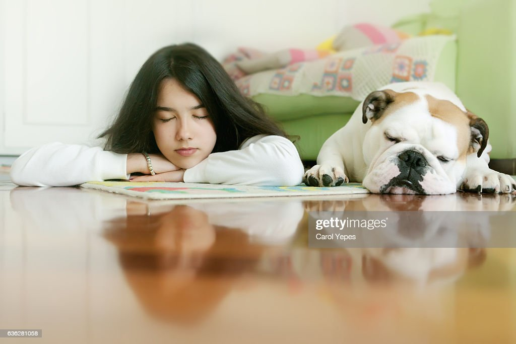 girl laying with slept dog : Stock Photo