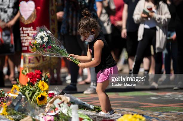 A girl lays flowers at a memorial for George Floyd on June 3 2020 in Minneapolis Minnesota Former police officer Derek Chauvin has been charged with...