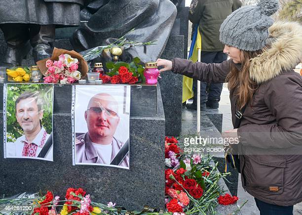 A girl lays flowers on February 23 2015 above pictures of two people who were killed on February 22 in northeastern Ukrainian city of Kharkiv in an...