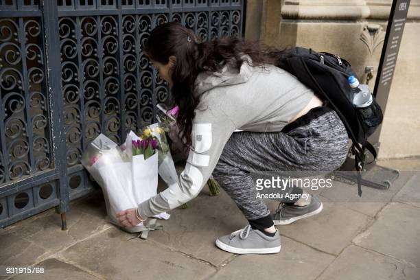 A girl lays flowers to the gate of Gonville and Caius College in Cambridge United Kingdom to pay tribute to world renowned physicist Stephen Hawking...