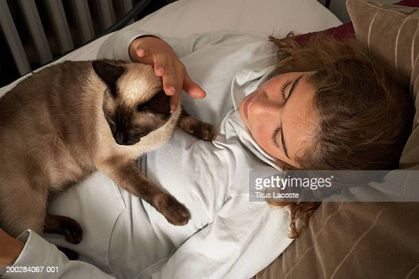 girl (12-14) leaning against cushions with cat lying on stomach - siamese cat stock pictures, royalty-free photos & images