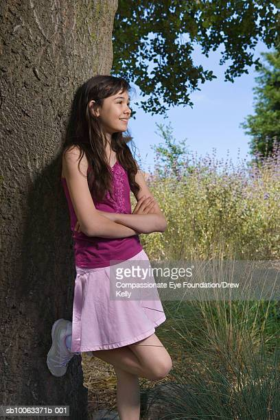 Girl (12-13 years) leaning against tree