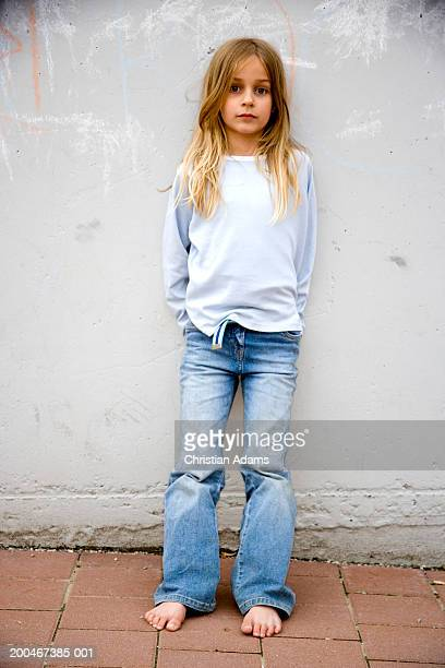 girl (5-7) leaning against wall, portrait - girls barefoot in jeans stock photos and pictures
