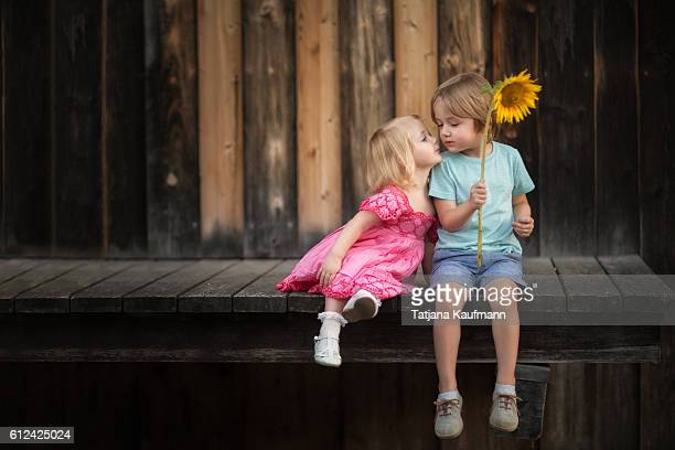 Girl leaning in to kiss Boy with a Flower