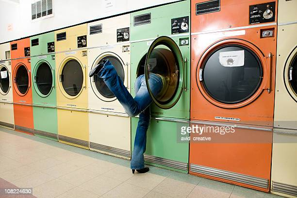 Girl Leaning into Laundromat Washer to Get Clothes