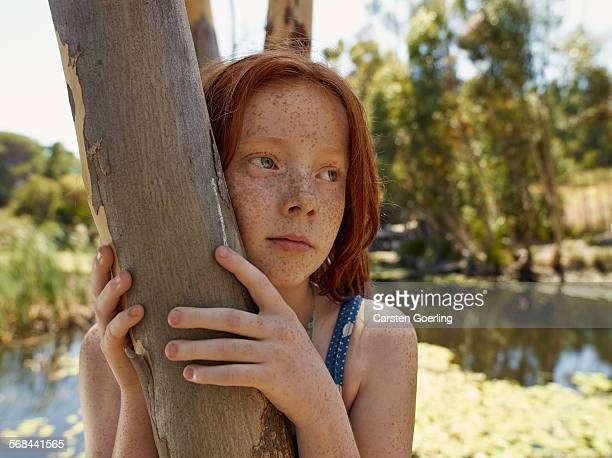 girl leaning on a tree