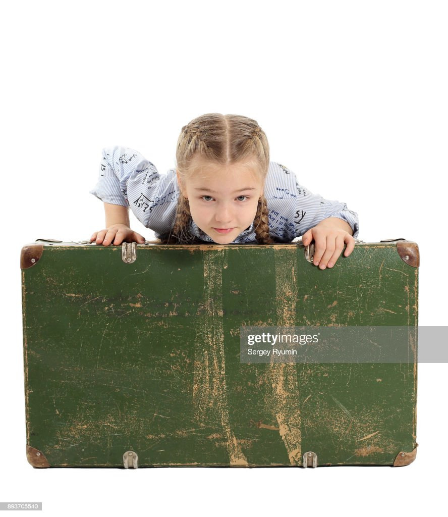 a girl leaning on an old suitcase stock photo getty images