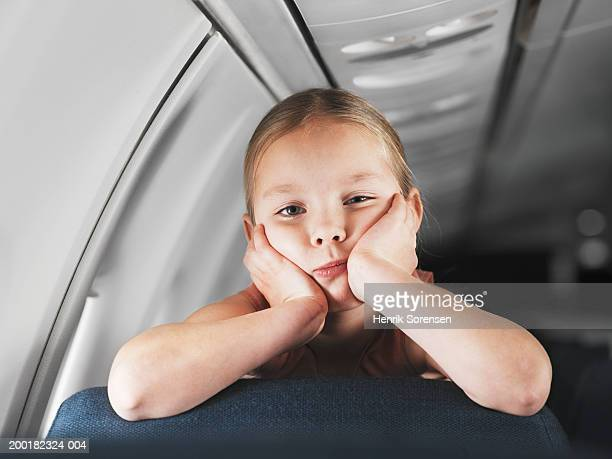 Girl (5-7) leaning on back of aeroplane seat, face in hands, portrait