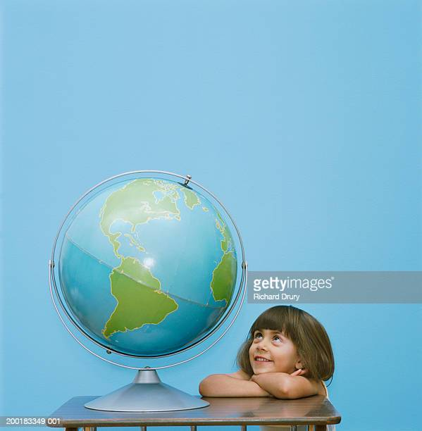 Girl (3-5) leaning on desk looking up at globe, smiling