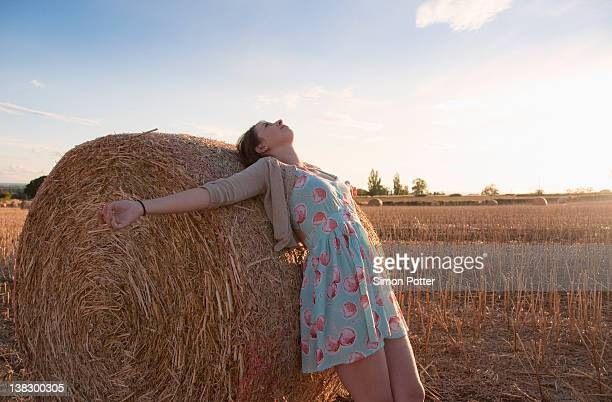 Girl leaning on haystack in field