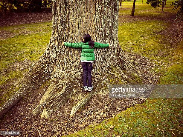 Girl leaning on tree.