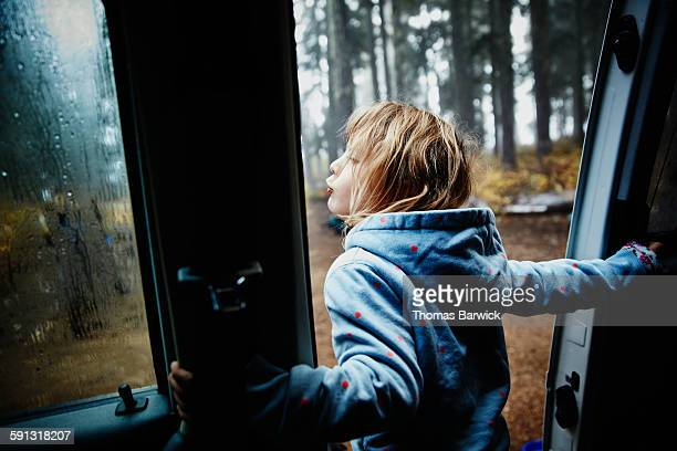 Girl leaning out door of camper van in the morning