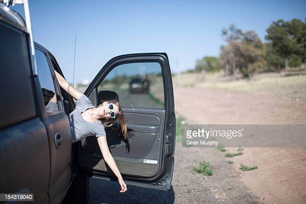 Girl leaning out of a car door
