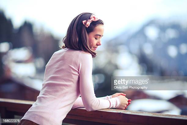 Girl Leaning over Balcony in Swiss Mountains