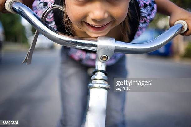 Girl leaning over bicycle handlebars