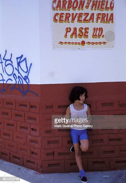 A girl leans against a graffititagged wall near a Cerveza beer sign Juarez Mexico late 1980s