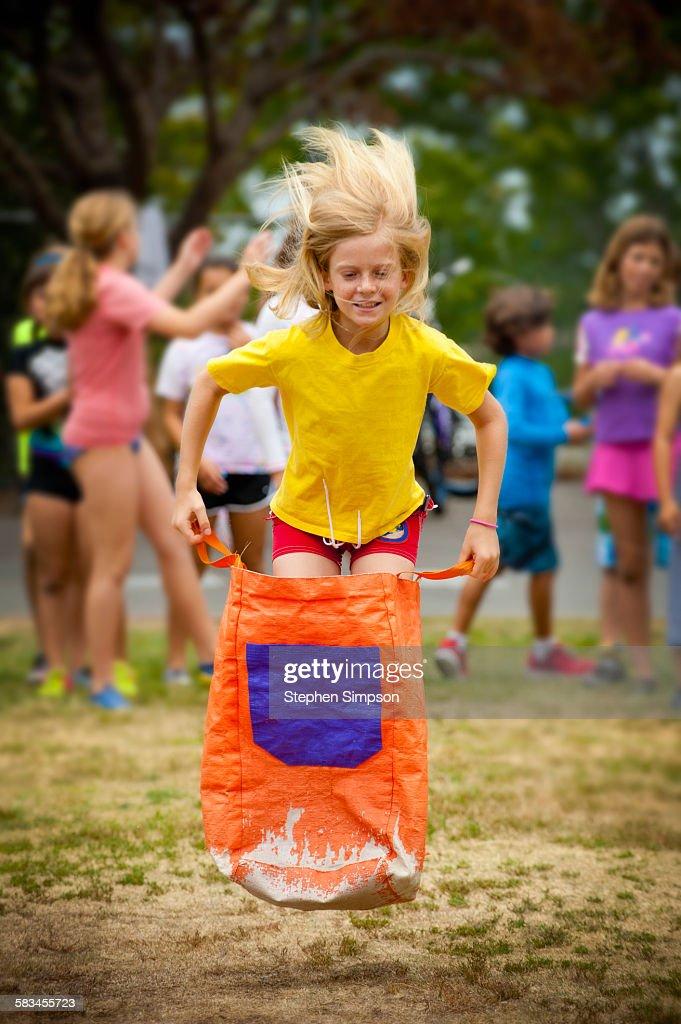 girl leaping on school sack race : Stock Photo