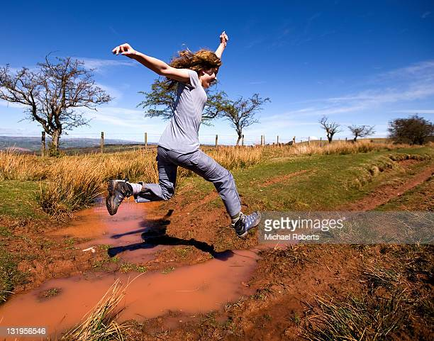 Girl leaping over puddle