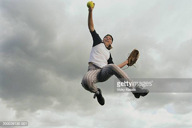 girl (13-15) leaping to catch softball, low angle view - catching stock pictures, royalty-free photos & images