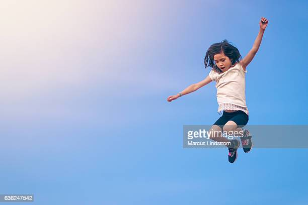 girl leaping towards the sky - blue shorts stock pictures, royalty-free photos & images
