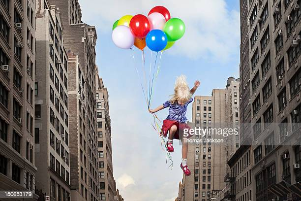 Girl leaping with balloons