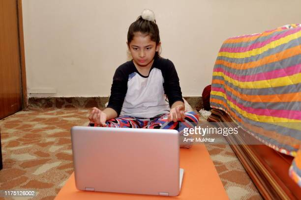 girl learning and doing yoga exercises by watching youtube on laptop - punjab pakistan stock pictures, royalty-free photos & images