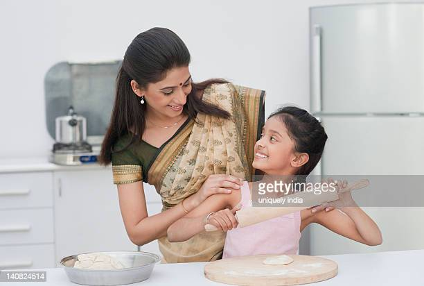 Girl learning cooking with the help of her mother