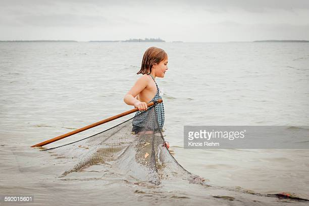 girl learning how to use traditional fishing net, sanibel island, pine island sound, florida, usa - estuary stock pictures, royalty-free photos & images