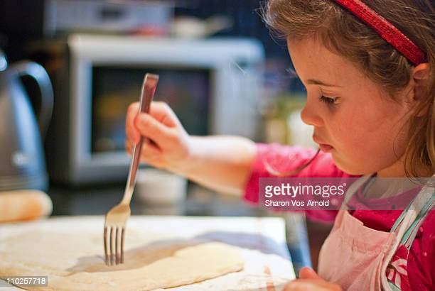 Girl learning to cook, making a pizza base
