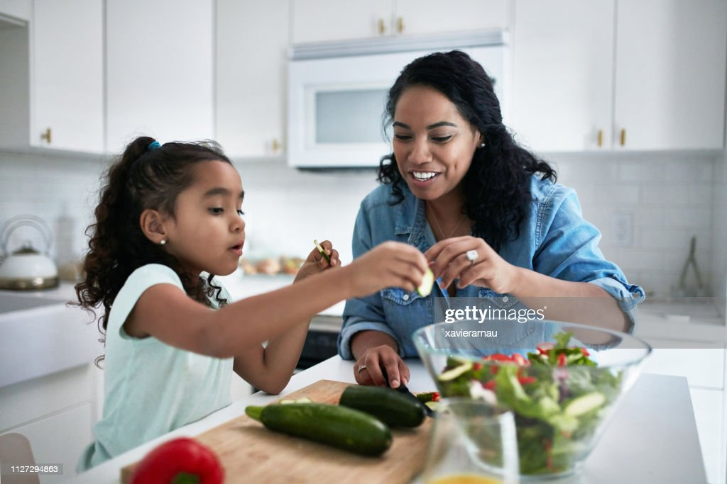 Girl learning to prepare meal from mother : Stock Photo