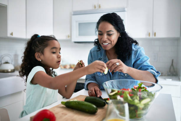 girl learning to prepare meal from mother - preparation stock pictures, royalty-free photos & images